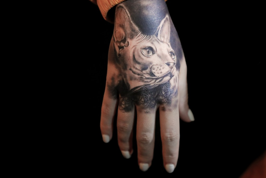 In this Saturday, Nov. 2, 2019, a tattoo depicting a cat decorates a woman's hand during the 10th International Tattoo Convention in Bucharest, Romani...
