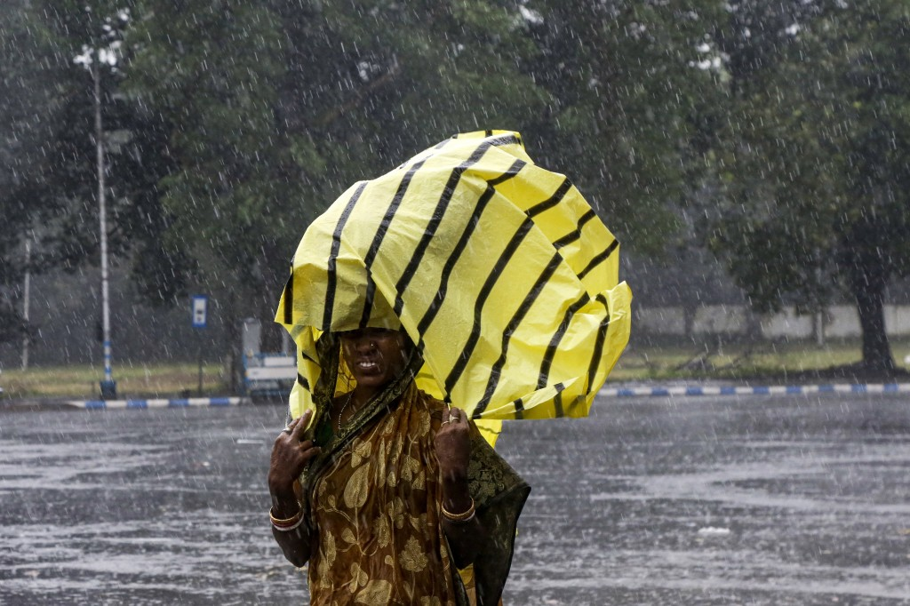 A woman covers her head with a plastic sheet as it rains in Kolkata, India, Saturday, Nov. 9, 2019. Authorities in nearby Bangladesh put more than 50,...