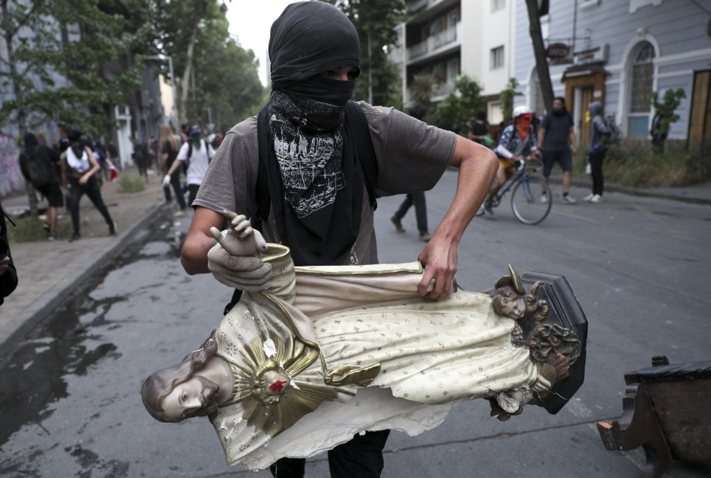 A masked demonstrator carries a statue of Jesus Christ that he took from a church to be added to a barricade, in Santiago, Chile, Friday, Nov. 8, 2019...