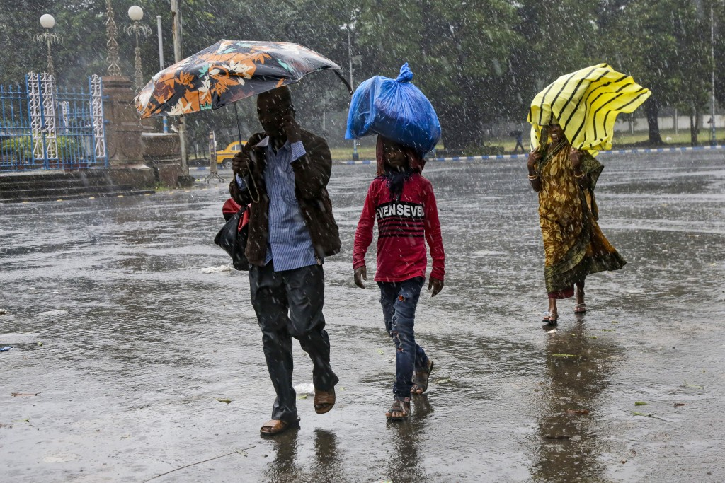 Indians walk in the rain in Kolkata, India, Saturday, Nov. 9, 2019. Authorities in nearby Bangladesh put more than 50,000 volunteers on standby and re...