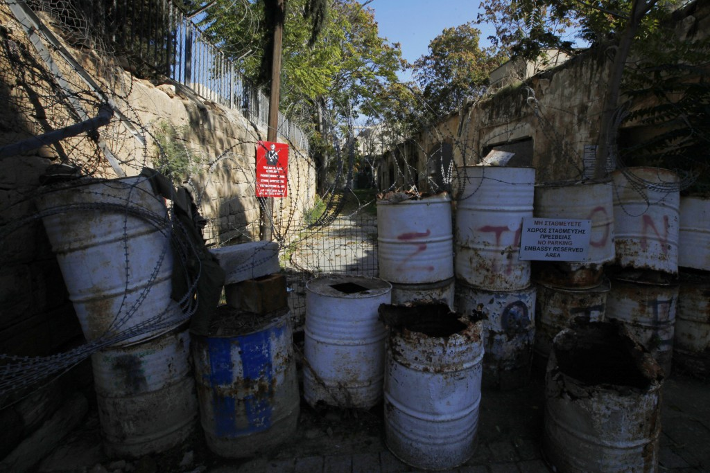In this photo taken on Thursday Nov. 7, 2019, a Turkish military sign is seen behind barrels that block a road from the Greek Cypriot south to the Tur...