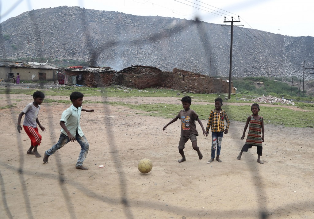 In this Oct. 23, 2019, photo, children of laborers who work in coal fields play a game of soccer in the village of Rajapur in Jharia, a remote corner ...