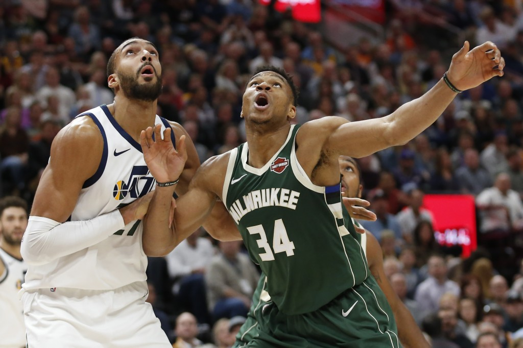 Utah Jazz center Rudy Gobert, left, and Milwaukee Bucks forward Giannis Antetokounmpo (34) look for a rebound during the first half of an NBA basketba...