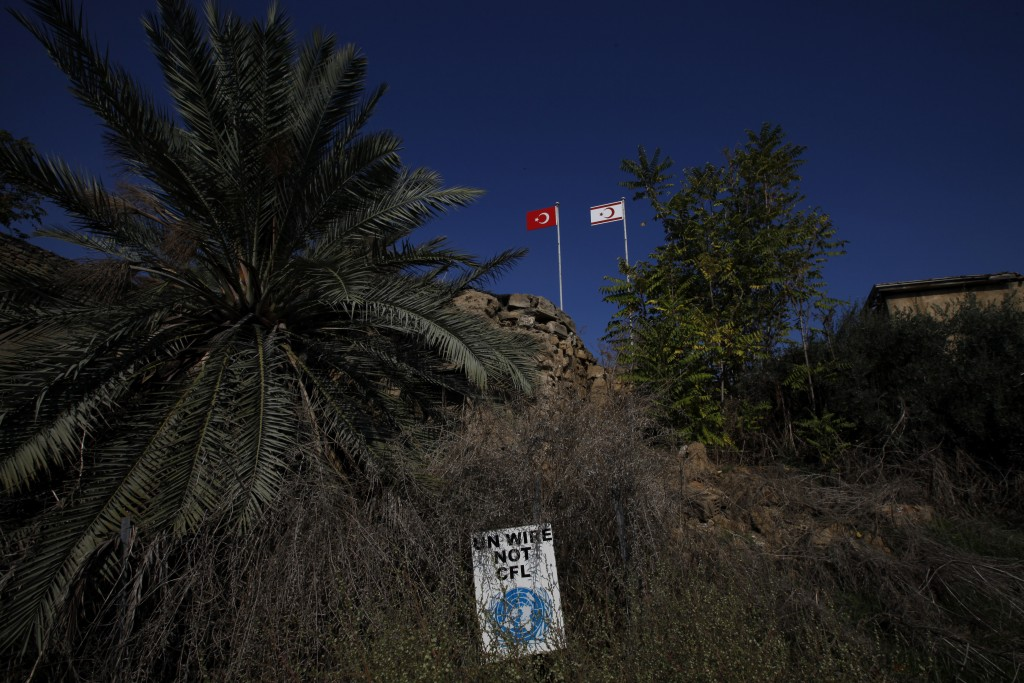 In this Tuesday Nov. 5, 2019, a Turkish, left, and a Turkish Cypriot breakaway flags are seen at a guard military post by a U.N sing inside the U.N bu...