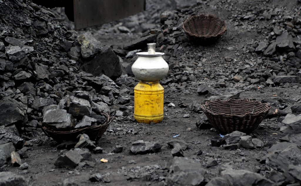 In this Oct. 23, 2019, photo, a metal vessel filled with drinking water stands at a coal loading site in the village of Godhar in Jharia, a remote cor...
