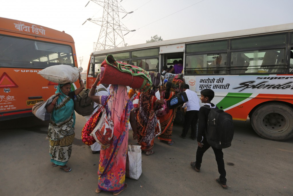 Hindu pilgrims wait in a queue to board a bus as authorities turned back thousands who were congregating for a religious event on Tuesday in Ayodhya, ...