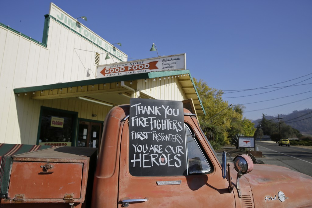 In this Wednesday, Nov. 6, 2019 photo, a sign thanking firefighters is displayed on the historic truck outside the Jimtown Store in Healdsburg, Calif....
