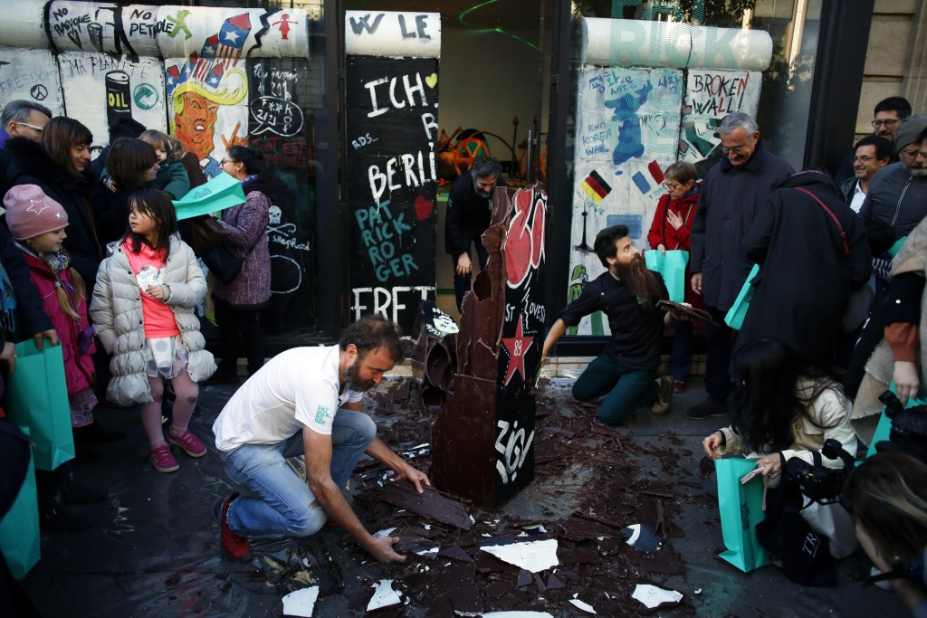 French chocolate maker Patrick Roger, center left, destroys a reproduction of the Berlin wall in chocolate, to mark the 30th anniversary of the fall o...
