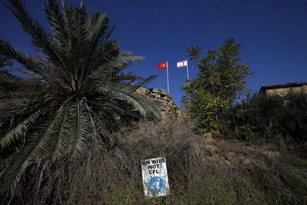 In this photo taken on Tuesday Nov. 5, 2019, a Turkish, left, and a Turkish Cypriot breakaway flags are seen at a military guard post by a U.N sing in...