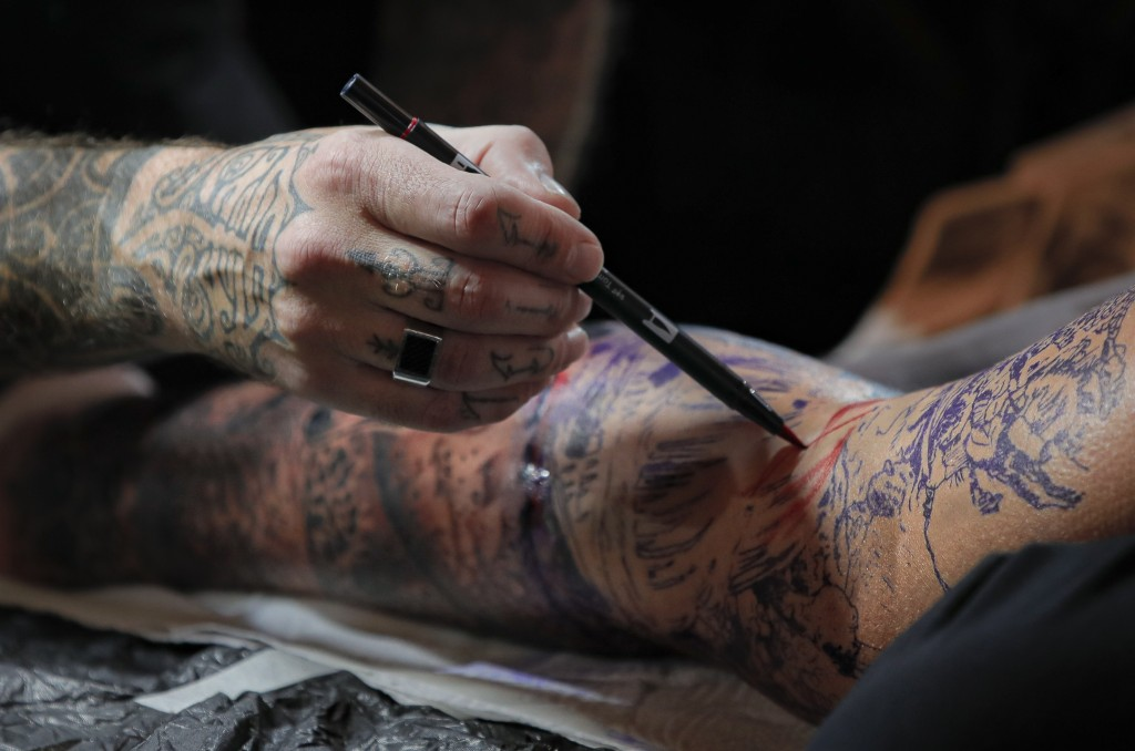 In this Saturday, Nov. 2, 2019, a tattoo artist pains the base of a tattoo on a man's leg during the 10th International Tattoo Convention in Bucharest...