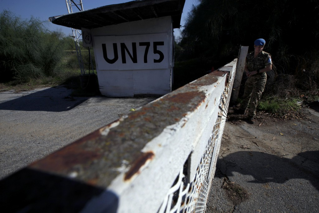 In this photo taken on Tuesday Nov. 5, 2019, a U.N peacekeeper stands by a gate crossing inside the U.N buffer zone that divides the Greek Cypriot sou...