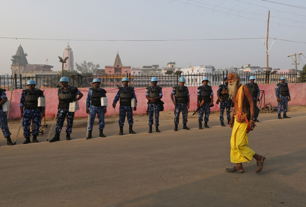 A Sadhu, Hindu holy man, walks past security officers standing guard in Ayodhya, India , Saturday, Nov. 9, 2019. India's security forces were on high ...