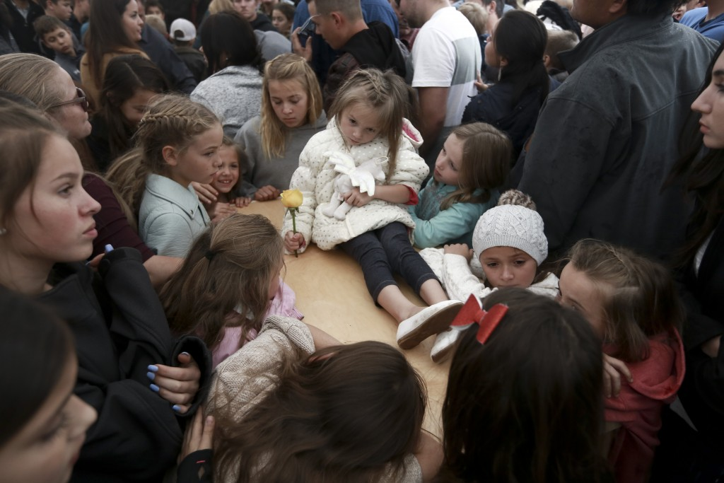 A child sits on top of a coffin as family and friends pay their final respects to Rhonita Miller, and four of her young children; Krystal and Howard, ...