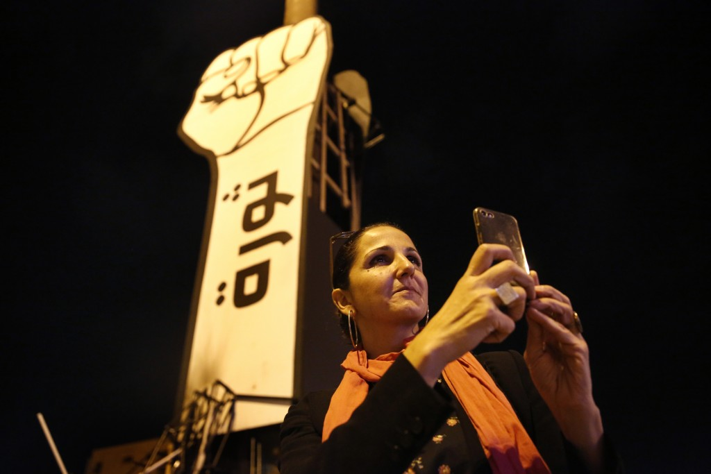 In this Friday, Nov. 8, 2019 photo Singer Tania Saleh takes pictures by her mobile phone at the martyrs square where the ongoing anti-government take ...
