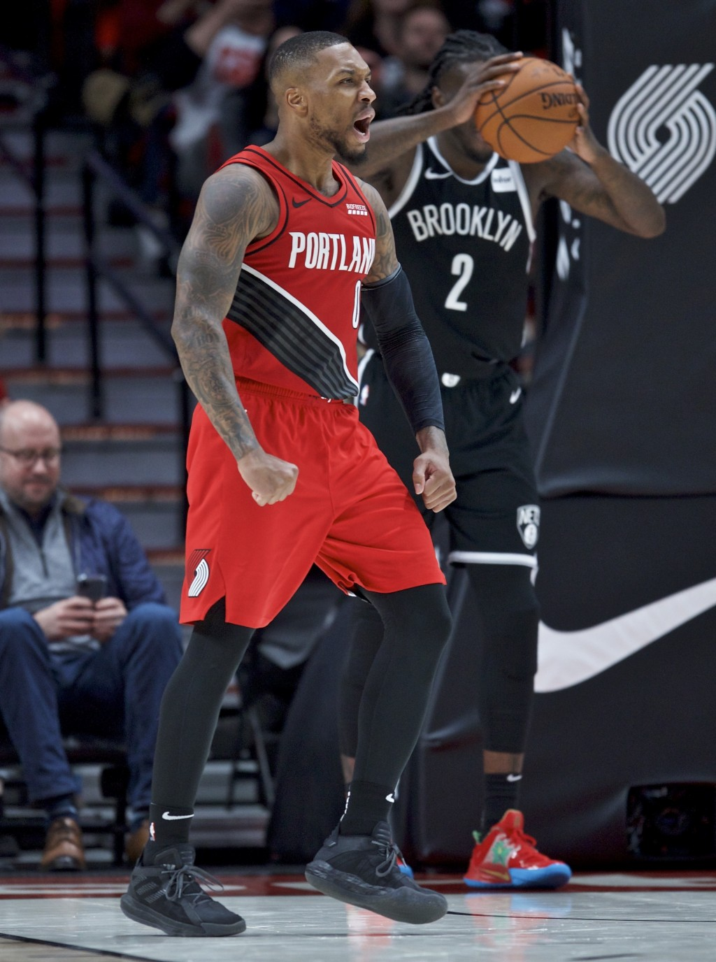 Portland Trail Blazers guard Damian Lillard reacts after scoring his 50th point of the night, during the second half of the team's NBA basketball game...