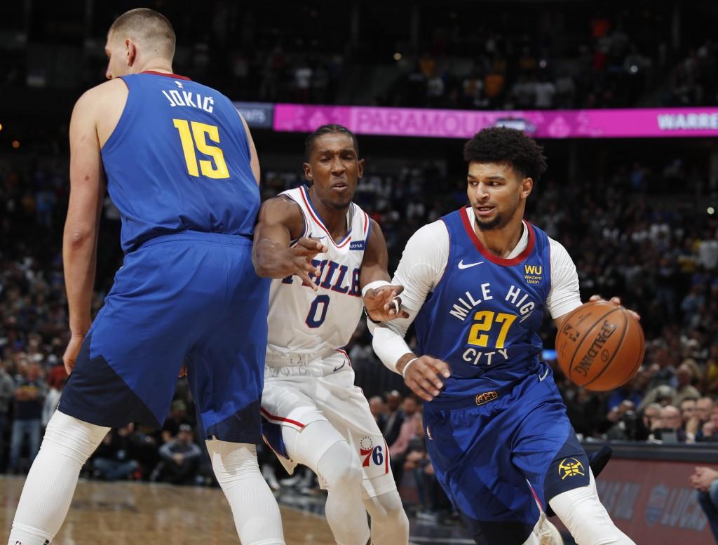 Philadelphia 76ers guard Josh Richardson, center, is hit as he tries to slip past a pick set by Denver Nuggets center Nikola Jokic, left, as Nuggets g...