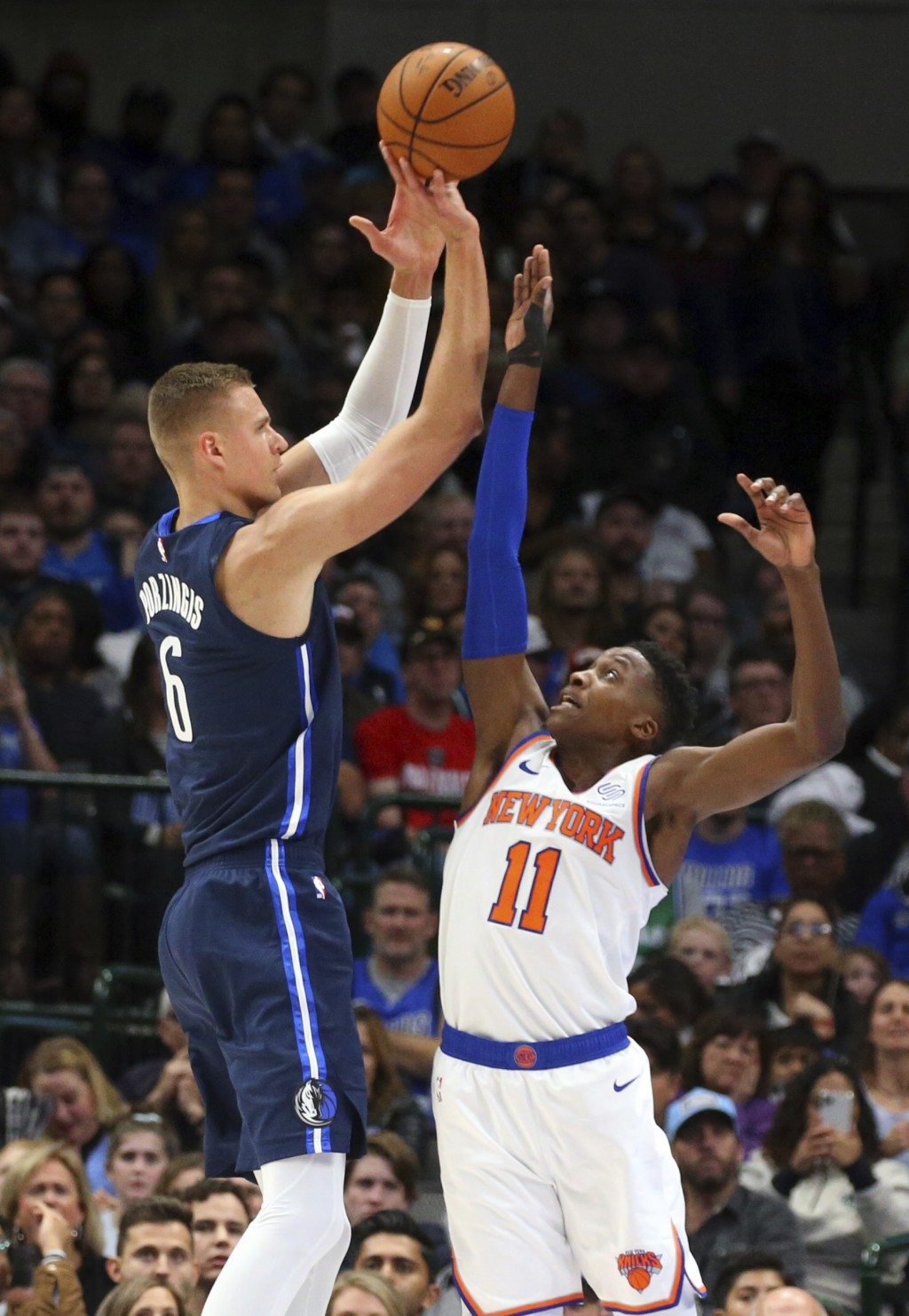 Dallas Mavericks forward Kristaps Porzingis (6) puts up a shot over New York Knicks guard Frank Ntilikina (11) in the first half of an NBA basketball ...