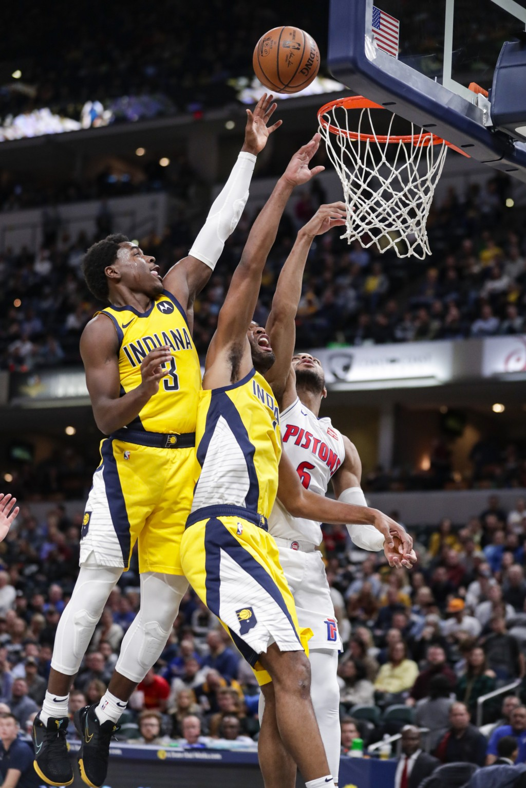 Detroit Pistons guard Bruce Brown (6) and Indiana Pacers guard Aaron Holiday (3) and forward T.J. Warren (1) go up for a rebound during the second hal...