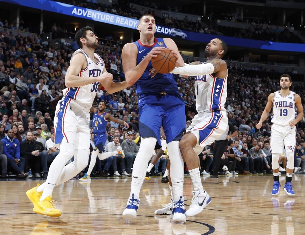 Denver Nuggets center Nikola Jokic, center, fights for control of the ball with Philadelphia 76ers guard Furkan Korkmaz, left, and forward Mike Scott ...