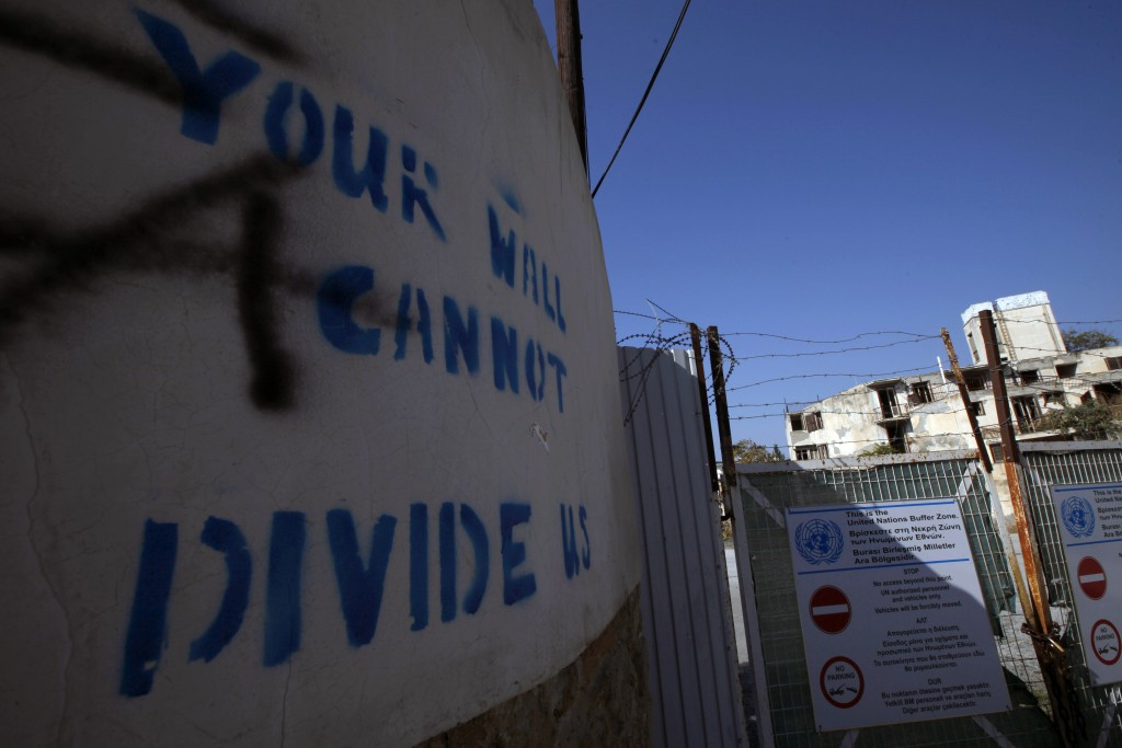"In this photo taken on Wednesday Nov. 6, 2019, graffiti on a wall reading ""Your wall can not divide us"" is seen at the U.N buffer zone by a fence that..."