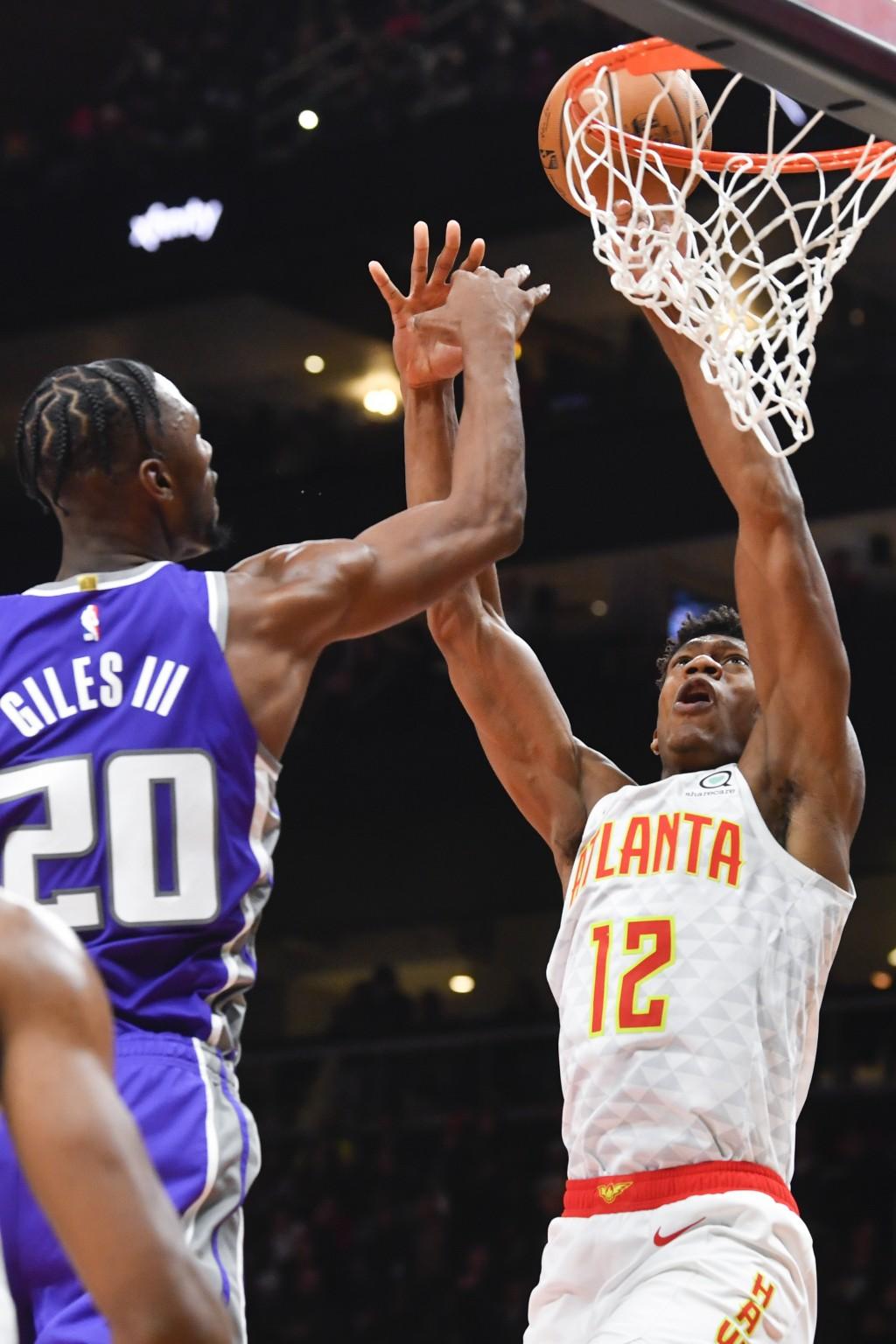Atlanta Hawks forward De'Andre Hunter (12) shoots as Sacramento Kings forward Harry Giles III (20) defends during the first half of an NBA basketball ...