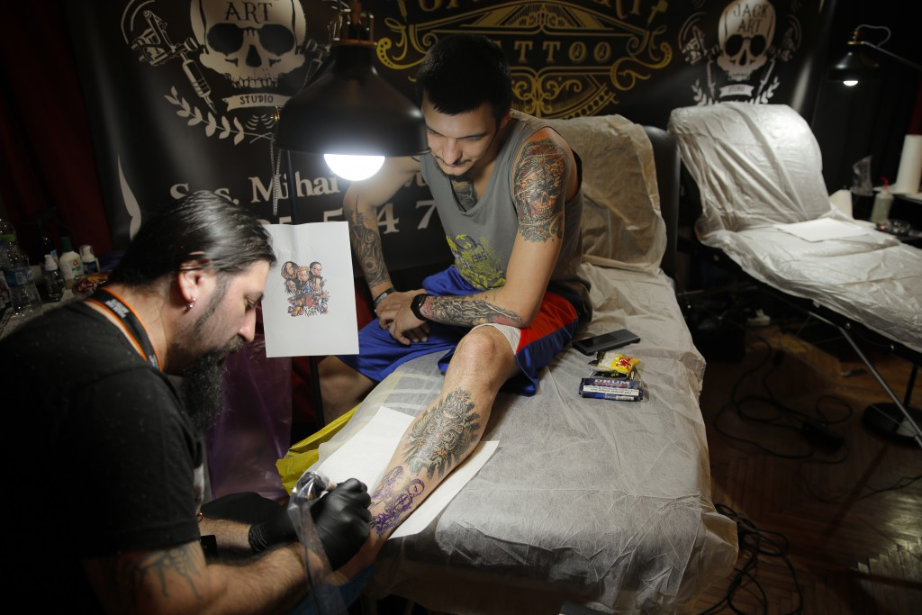 In this Saturday, Nov. 2, 2019, a man gets a new tattoo on his leg during the 10th International Tattoo Convention in Bucharest, Romania. (AP Photo/Va...