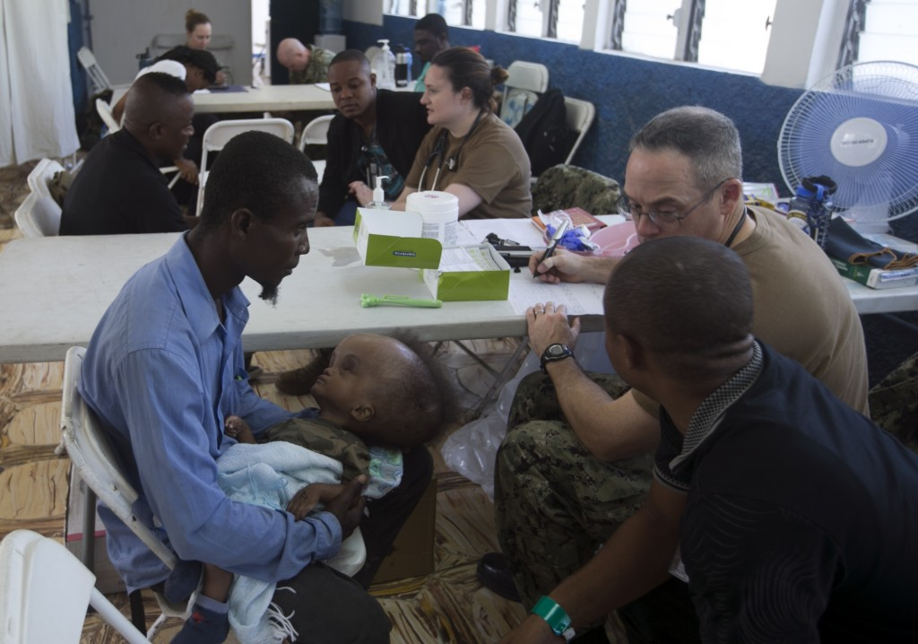 A man holds an ill baby as he sits with US military doctors who arrived on the U.S. Navy hospital ship USNS Comfort, as Haitians get free treatment, a...