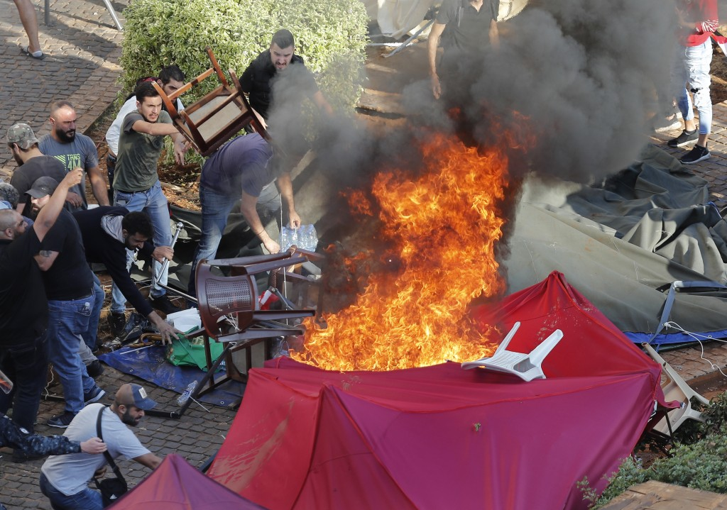 FILE - In this Tuesday, Oct. 29, 2019 file photo, supporters of the Shiite Hezbollah group burn tents in the camp set up by anti-government protesters...