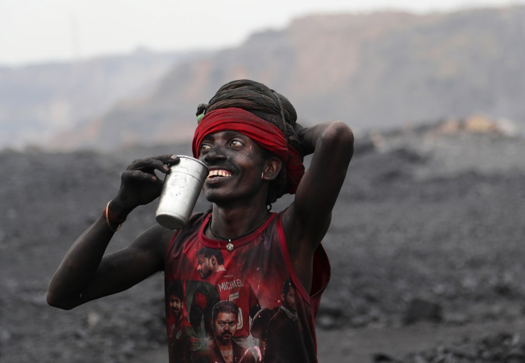 In this Oct. 23, 2019, photo, a laborer smiles as he prepares to drink water during a break from loading coal into trucks for transportation in the vi...