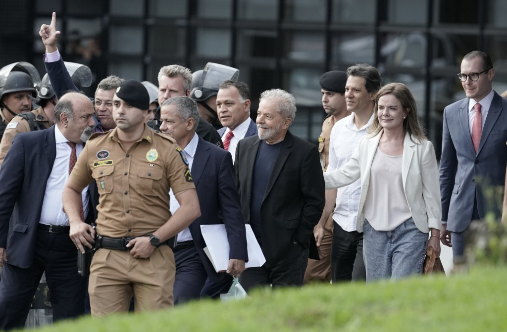 Brazil's former President Luiz Inacio Lula da Silva, center, exits the the Federal Police headquarters where he was imprisoned on corruption charges i...