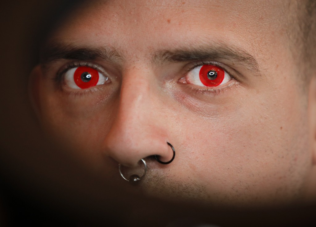 In this Saturday, Nov. 2, 2019, a man wearing red contact lenses is illuminated by the lamp of a tattoo artist during the 10th International Tattoo Co...