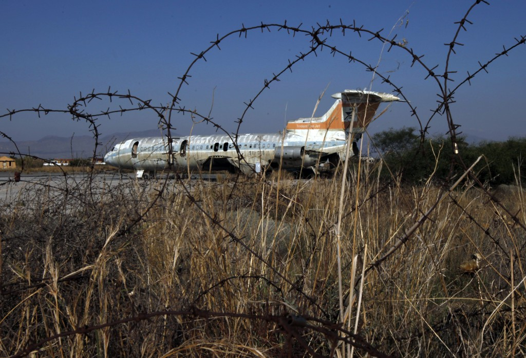 In this photo taken on Tuesday Nov. 5, 2019, an abandoned Cyprus airways aircraft is seen behind the barbed wires at the abandoned Nicosia airport ins...