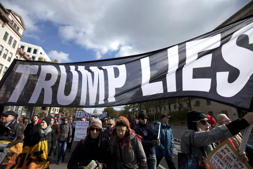Demonstrators march on Pennsylvania Avenue protesting against climate policies and to impeach President Donald Trump, in Washington, Friday, Nov. 8, 2...