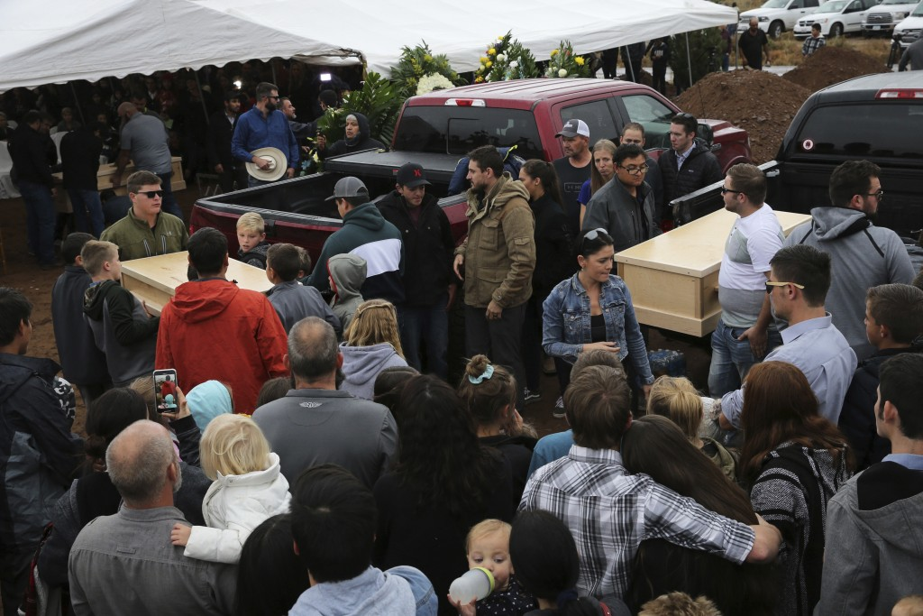 Family and friends unload the coffins that contain the remains of Rhonita Miller and four of her young children Krystal and Howard, and twins Titus an...