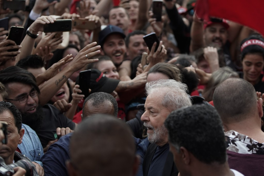 Brazil's former President Luiz Inacio Lula da Silva, bottom, is surrounded by supporters as he exits the Federal Police headquarters where he was impr...