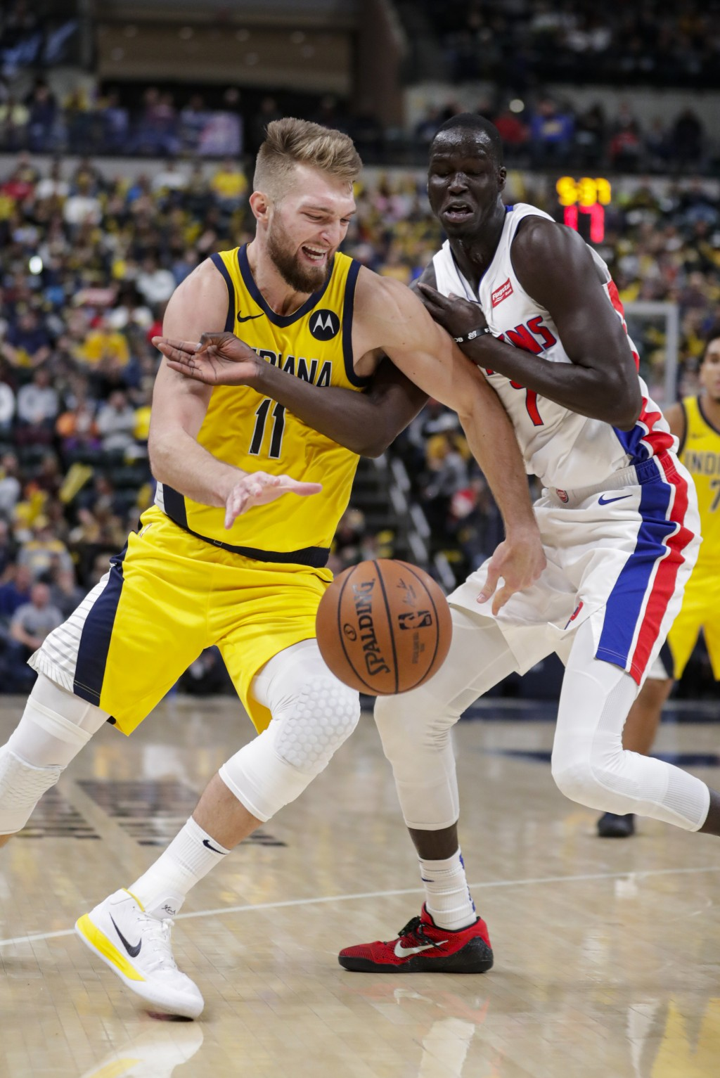 Indiana Pacers forward Domantas Sabonis (11) gets tangled up with Detroit Pistons forward Thon Maker (7) during the second half of an NBA basketball g...