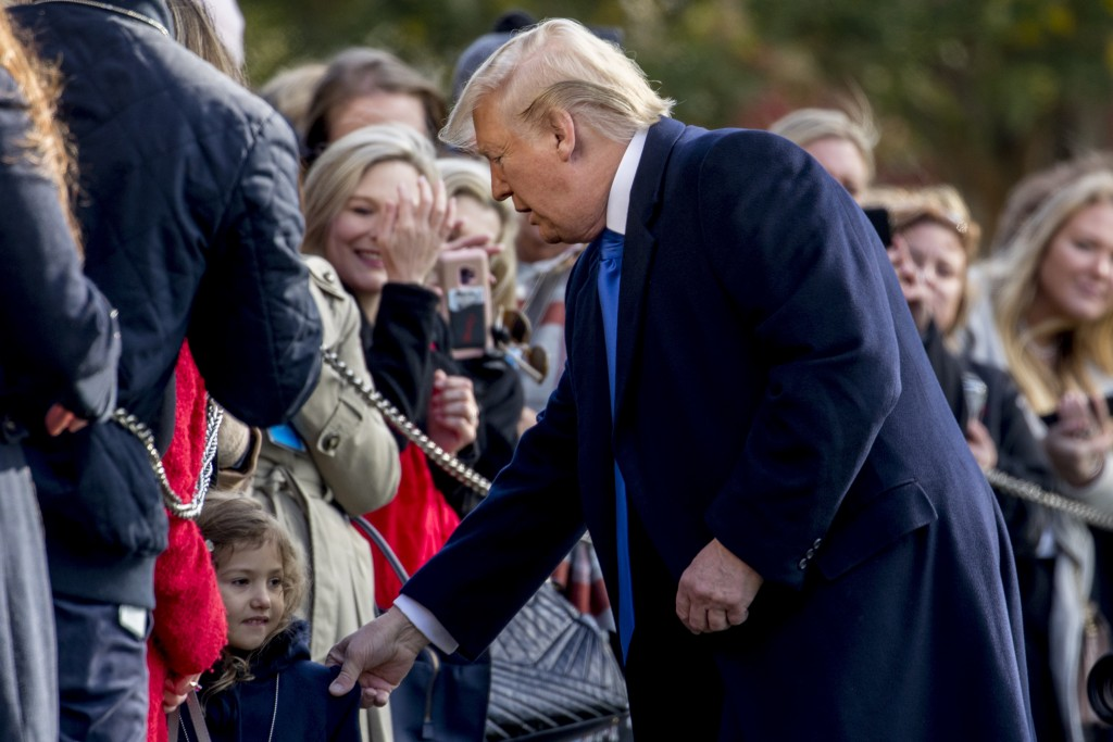 President Donald Trump pulls a girl out of the audience for a photograph on the South Lawn of the White House in Washington, Friday, Nov. 8, 2019, bef...