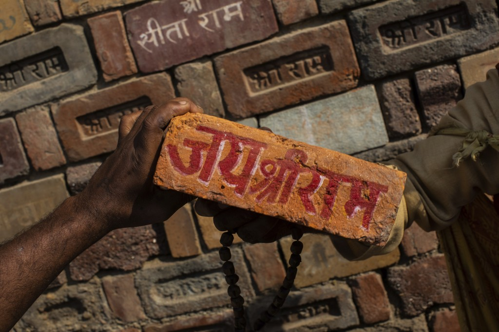 "FILE - In this Sunday, Nov. 25, 2018 photo, a man holds a brick reading ""Jai Shree Ram"" (Victory to Lord Ram) as bricks of the old Babri Mosque are pi..."
