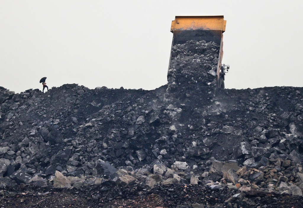 In this Oct. 23, 2019, photo, a laborer keeps watch as coal is unloaded from a truck in the village of Rajapur in Jharia, a remote corner of eastern J...