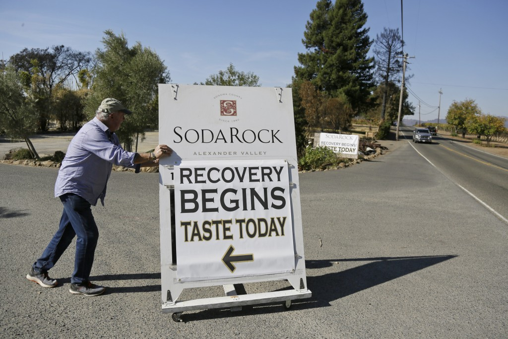 In this Wednesday, Nov. 6, 2019 photo, owner Ken Wilson rolls out a sign for passing motorists after opening a tasting area at his wildfire incinerate...