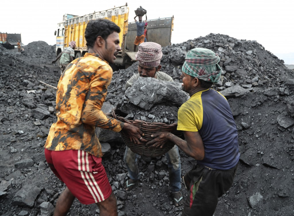 In this Oct. 23, 2019, photo, laborers lift a large basket filled with coal before loading it into a truck for transportation in the village of Godhar...