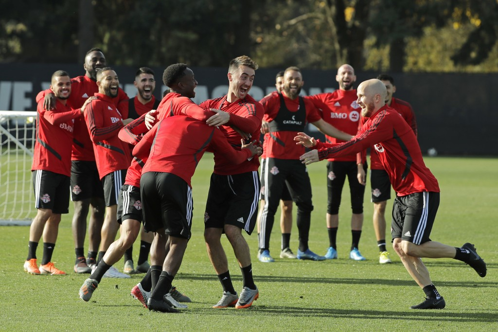 Toronto FC midfielder Michael Bradley, right, runs towards teammates as they share a lighthearted moment during a training session, Friday, Nov. 8, 20...