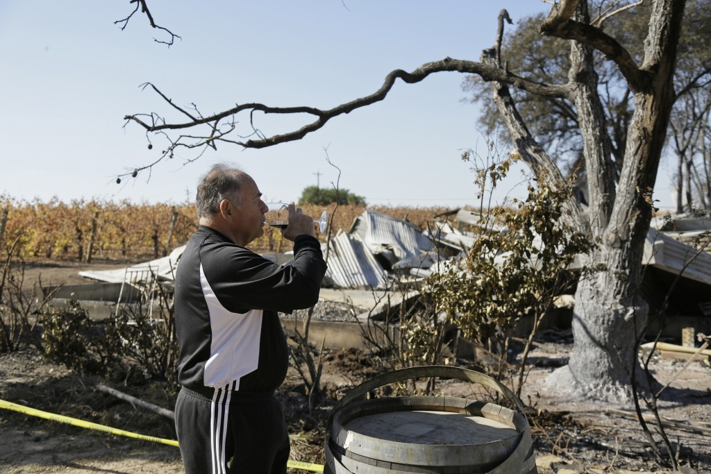 In this Wednesday, Nov. 6, 2019 photo, Izzy Lewkosky, of Kansas City, Kan., tastes a glass of Cabernet Sauvignon while looking out at the wildfire inc...