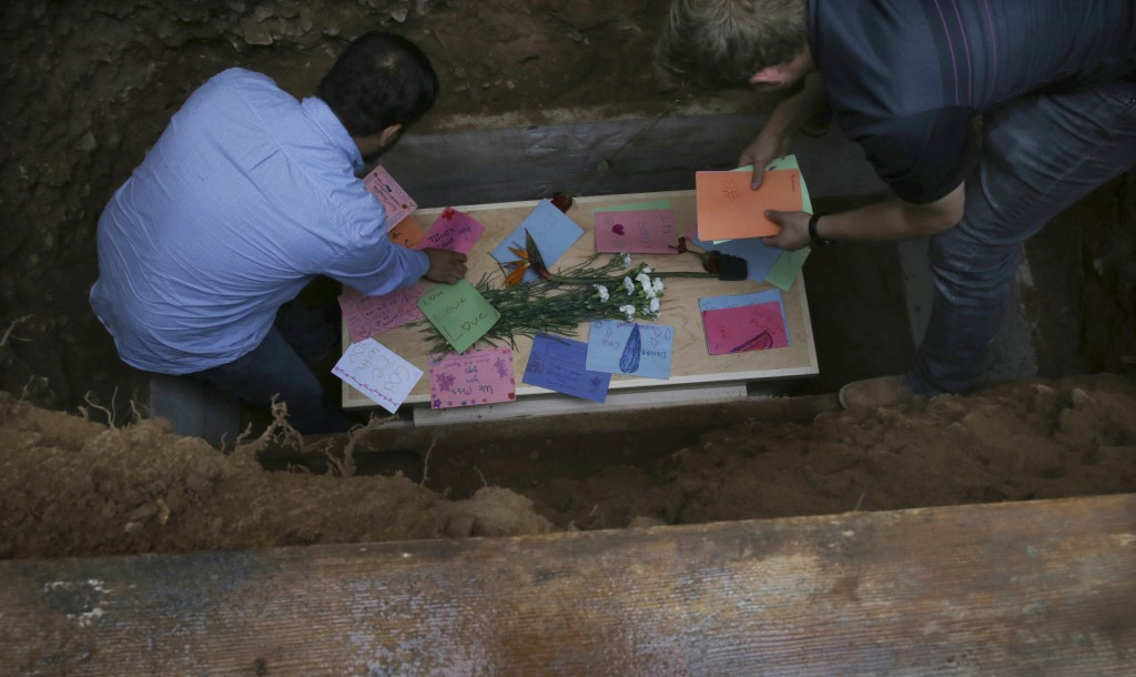Men arrange personal notes on the coffin that contains the remains of 12-year-old Howard Jacob Miller Jr., at the cemetery in Colonia Le Baron, Mexico...