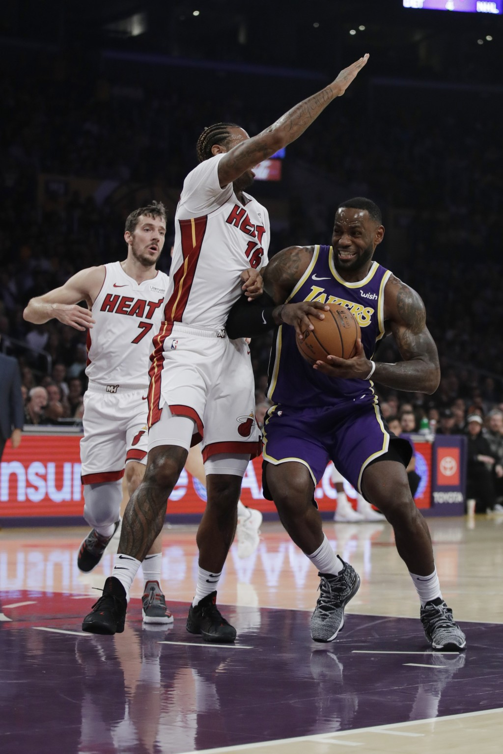 Los Angeles Lakers' LeBron James, right, is defended by Miami Heat's James Johnson during the first half of an NBA basketball game Friday, Nov. 8, 201...