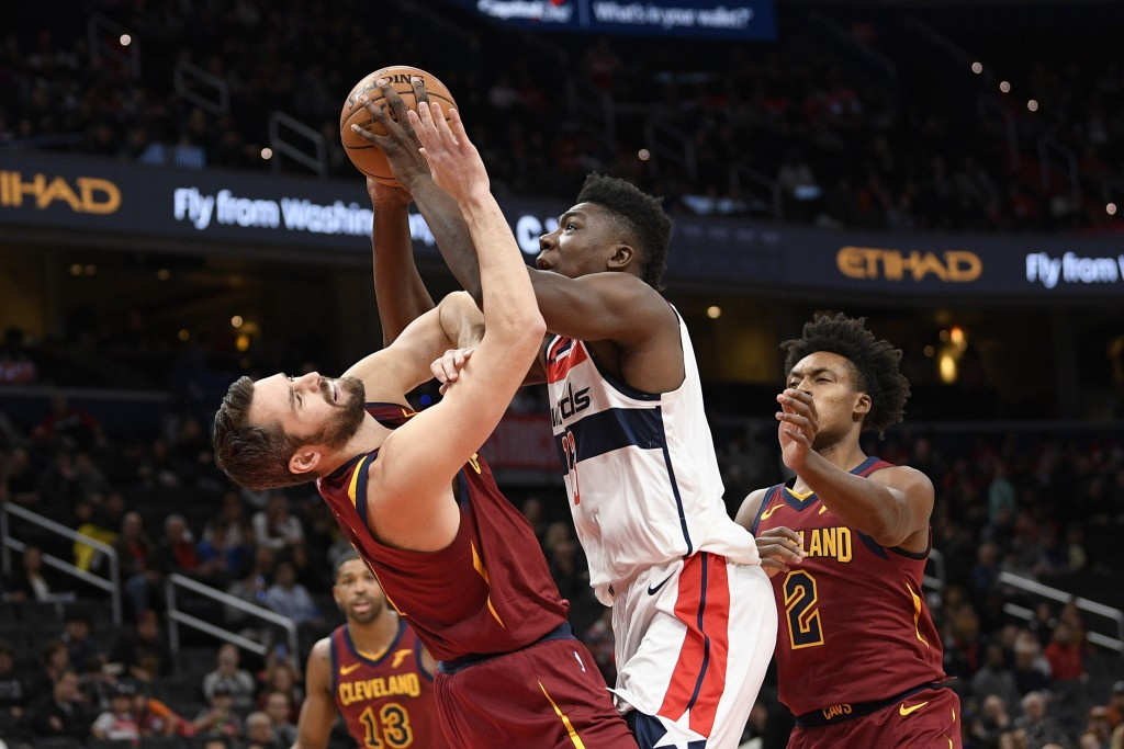 Washington Wizards center Thomas Bryant, center, goes to the basket between Cleveland Cavaliers forward Kevin Love, left, and guard Collin Sexton (2) ...