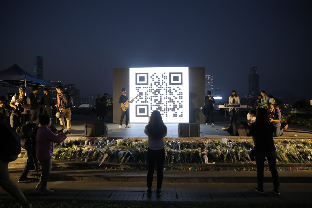 People attend a vigil for student Chow Tsz-Lok in Hong Kong, Saturday, Nov. 9, 2019. Chow Tsz-Lok, the Hong Kong university student who fell off a par...