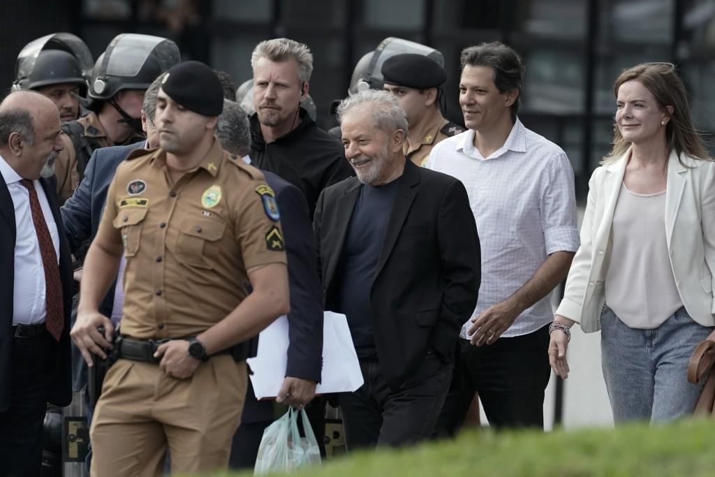 Brazil's former President Luiz Inacio Lula da Silva, center, smiles as he exits the the Federal Police headquarters where he was imprisoned on corrupt...