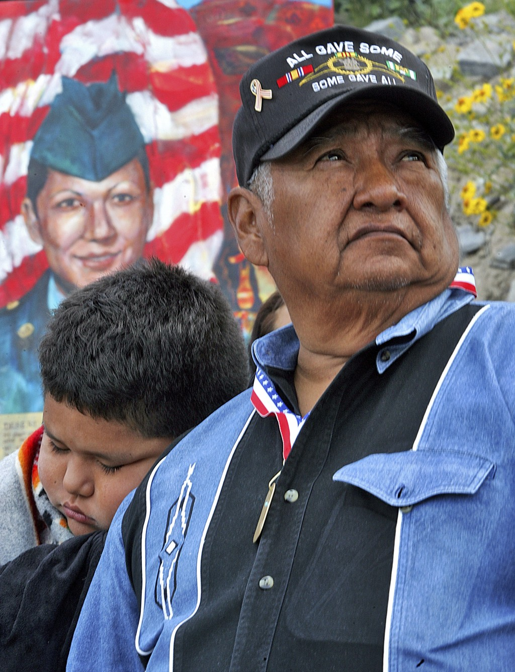 FILE - In this March 23, 2005, file photo, a portrait of U.S. Army Spc. Lori Piestewa, is shown behind her father, Terry Piestewa, right, and her son,...