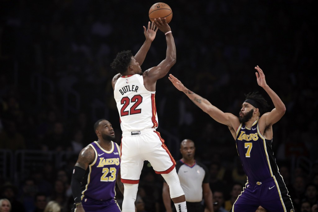 Miami Heat's Jimmy Butler (22) shoots over Los Angeles Lakers' JaVale McGee (7) and LeBron James (23) during the first half of an NBA basketball game ...